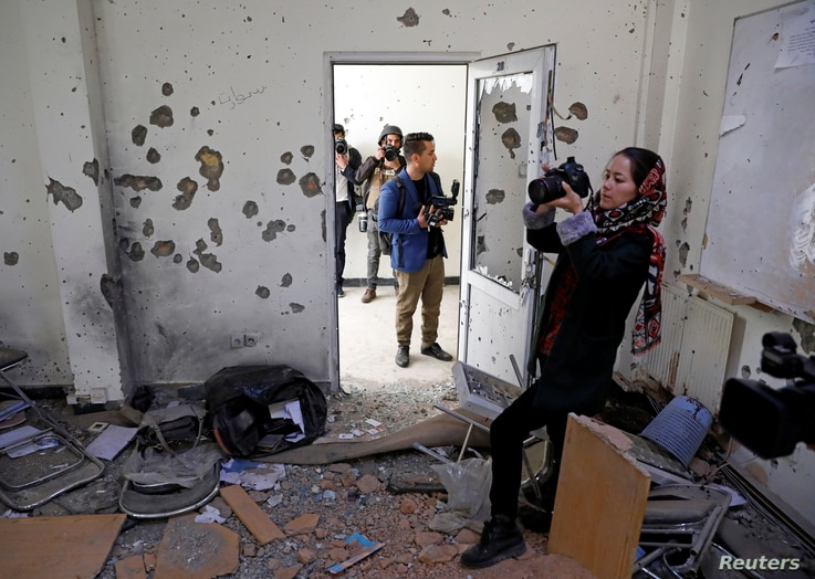 FILE - Afghan journalists film inside a classroom after yesterday's attack at the university of Kabul, Afghanistan, Nov. 3, 2020.