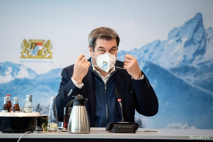 Bavaria's State Prime Minister Markus Soeder removes his protective mask before a so-called home office summit during the…