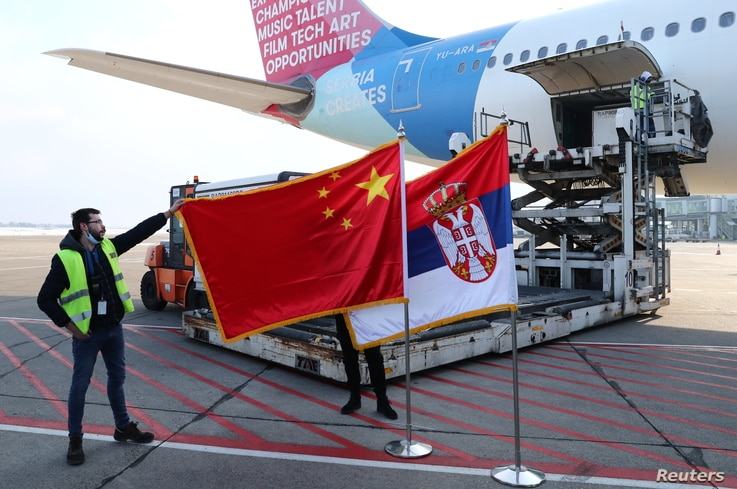 A man holds China's flag next to Serbia's flag as a plane transporting one million doses of Sinopharm's China National Biotec...