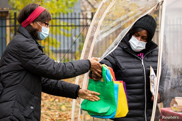Sister Jenthia Abell hands out COVID-19 survival kits to community members during a training session as part of an outreach…
