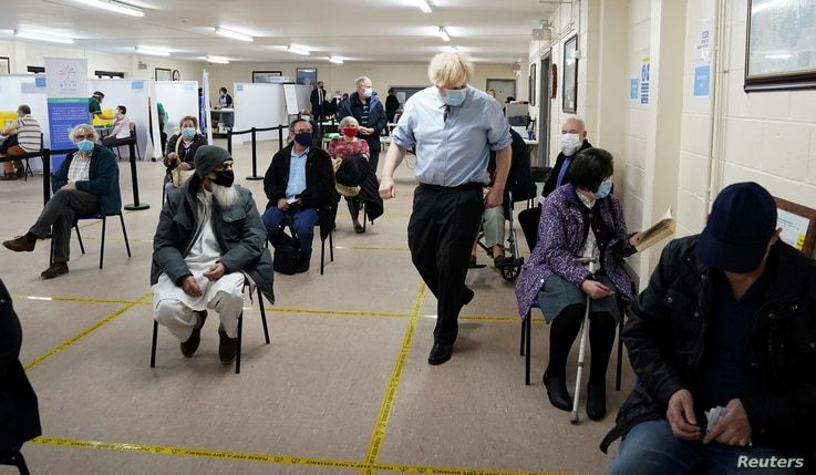 Britain's Prime Minister Boris Johnson walks past waiting patients as he visits a COVID-19 vaccination centre in Batley, West…