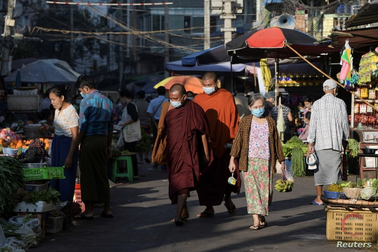 People walk at a market after army seized power in a coup in Yangon, Myanmar February 2, 2021. REUTERS/Stringer