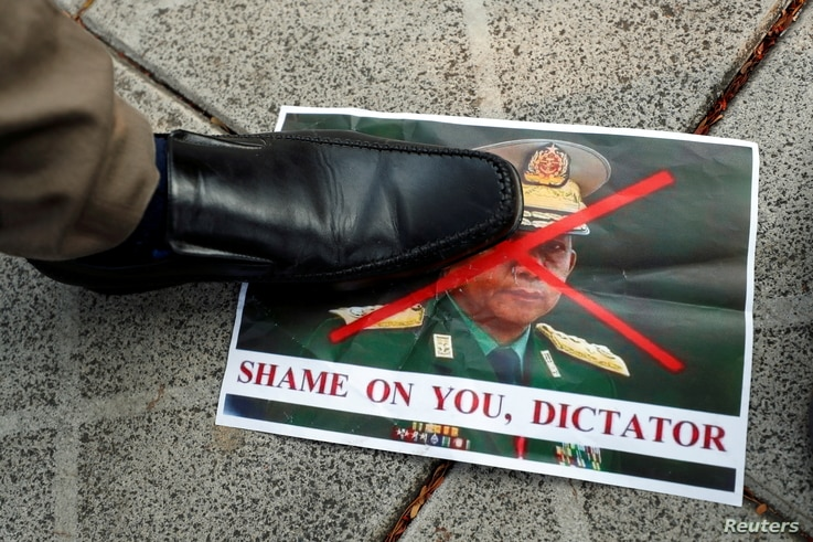 A person steps on a picture of Myanmar's army chief Min Aung Hlaing with his face crossed out after the military seized power…