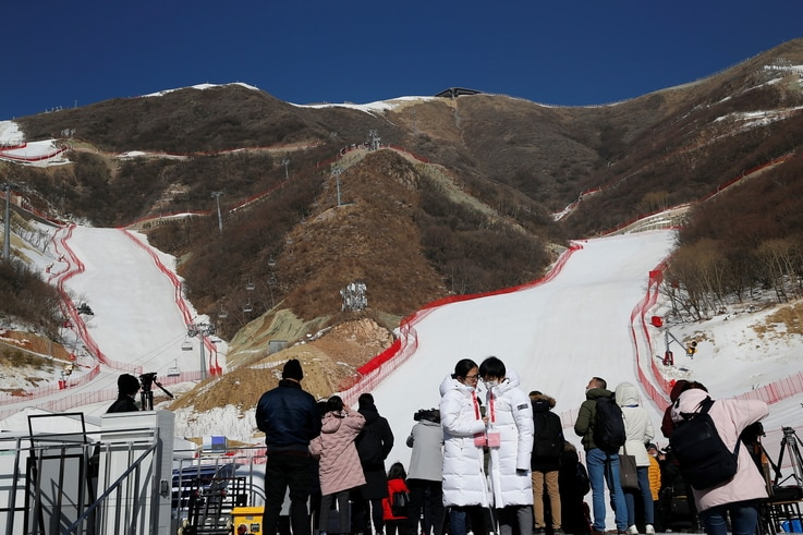 Journalists stand in front of ski slopes during an organised media tour to the National Alpine Skiing Centre, a venue of the…