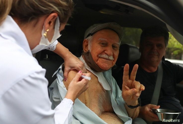 An elderly resident receives Sinovac's coronavirus disease (COVID-19) vaccine at a drive-thru centre for seniors citizens in…
