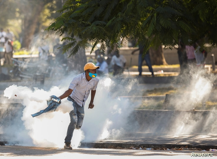 A demonstrator picks up a tear gas canister during protests against Haiti's President Jovenel Moise, in Port-au-Prince, Haiti…