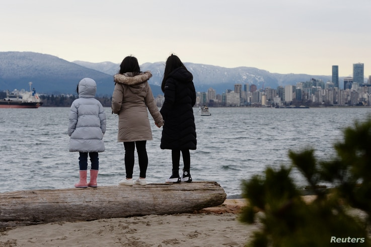 Maria Law, who emigrated from Hong Kong with her family, views the skyline with her daughters from Jericho Beach in Vancouver,…