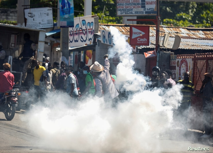 A man throws a tear gas canister back at the police during a protest against Haiti's President Jovenel Moise, in Port-au-Prince, Haiti, Feb. 10, 2021.