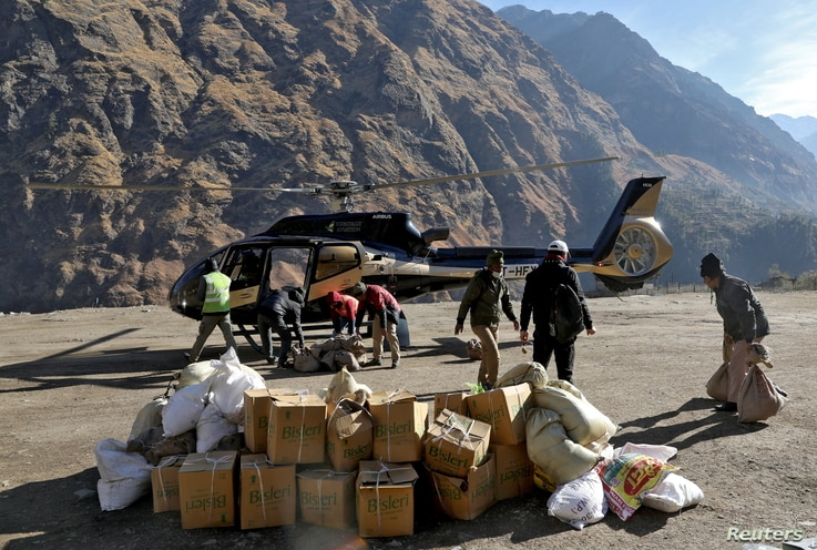 People load relief goods onto a helicopter for distribution in the affected areas, after a flash flood swept a mountain valley.