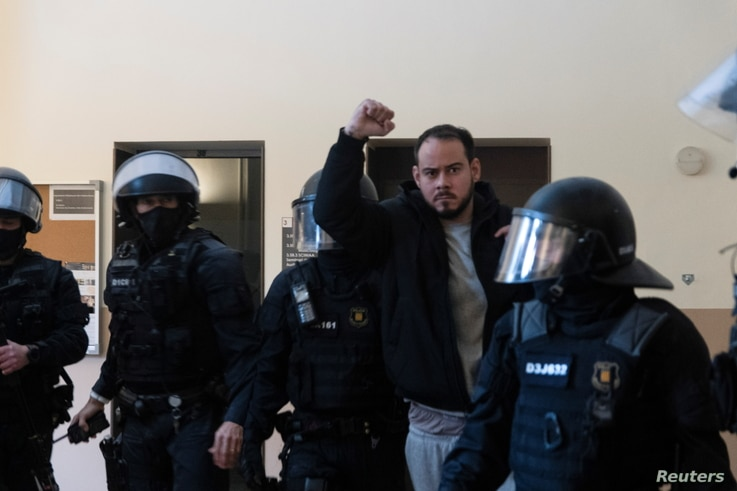 Spanish rapper Pablo Hasel reacts as he is detained by riot police inside the University of Lleida, after he was sentenced to jail time on charges including insulting the monarchy and glorifying terrorism, in Lleida, Spain, Feb. 16, 2021.