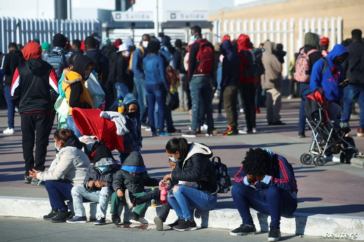 Migrants gather at the El Chaparral border crossing point to seek asylum in the U.S., in Tijuana, Mexico February 19, 2021…