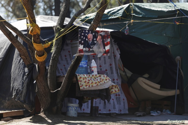 A campaign poster of U.S. President Joe Biden hangs on a tree at a migrant encampment in Matamoros, Mexico February 19, 2021…