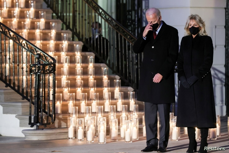 U.S. President Joe Biden makes the sign of the cross at the conclusion of a moment of silence as he and his wife Jill Biden…
