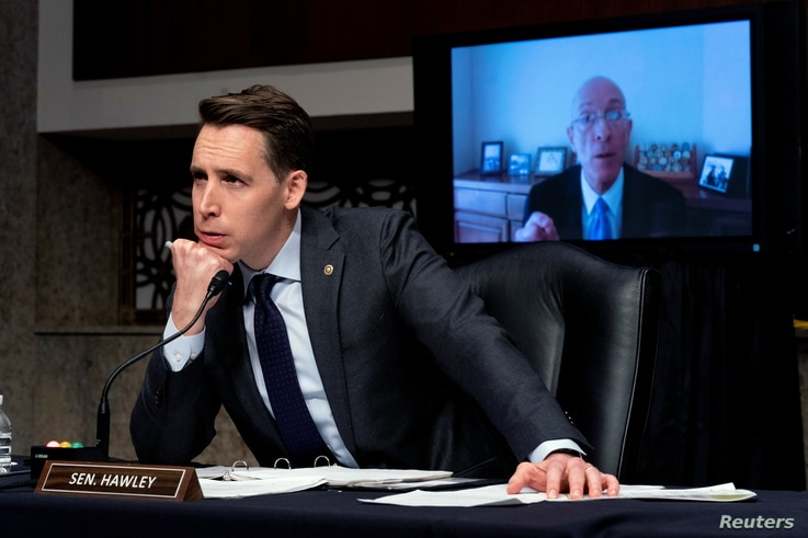 Sen. Josh Hawley, R-Mo., left, listens to former Sergeant at Arms Paul Irving testify via teleconference during a Senate…