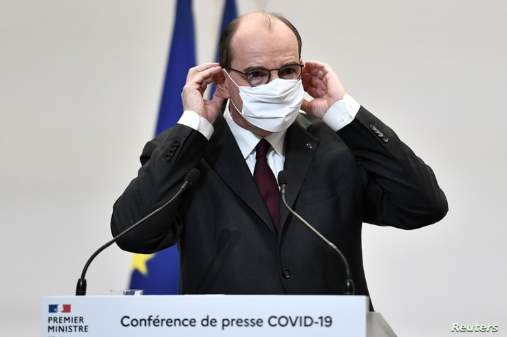 French Prime Minister Jean Castex touches his protective face mask during a press conference on the government's current…