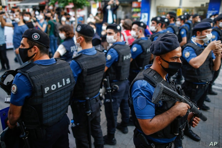 Turkish police officers in riot gear, wearing masks to protect from the spread of coronavirus, block supporters of pro-Kurdish…