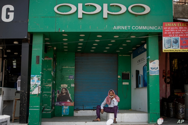 An Indian man speaks on his mobile phone in front of a shop selling OPPO phones, a Chinese consumer electronics company, in…