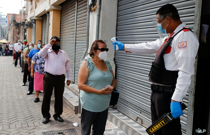 A security guard takes a woman's temperature as a precaution against the new coronavirus, as she lines up to enter a bank in...