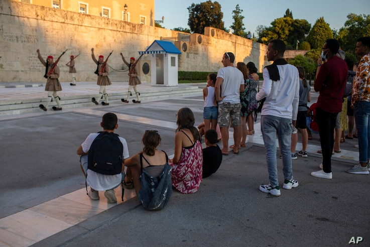 Tourists look at the changing of presidential guards ceremony outside the Greek parliament , in Athens, on Friday, July 31,…