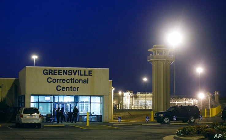 FILE - In this Sept. 23, 2010 file photo prison guards stand outside the entrance to the Greensville Correctional Center, where…