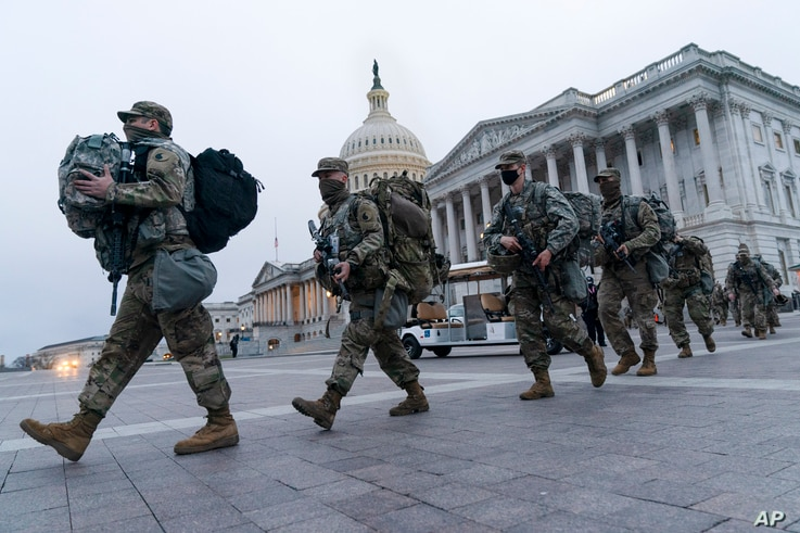 National Guard soldiers walk out of the U.S. Capitol, Saturday, Jan. 16, 2021, in Washington, as security is increased ahead of…