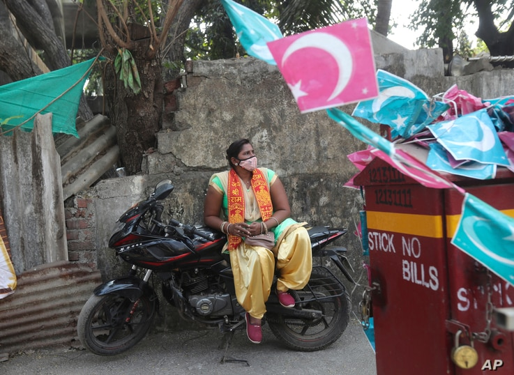 A Bharatiya Janata Party supporter wearing mask rests on bike as she waits to take part in a protest against The Amazon Prime Video web series Tandav in Mumbai, India, Jan 19, 2021.