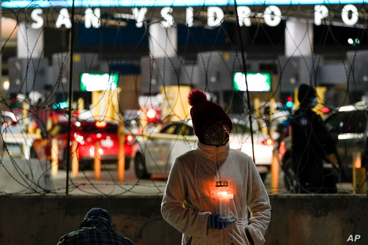 A woman holds a candle during a vigil in support of migrants as she stands at the entrance to the San Ysidro Port of Entry…