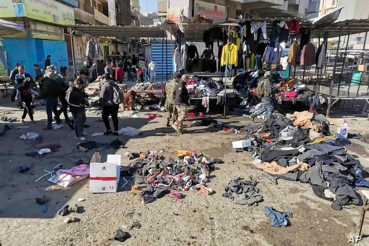FILE — People and security forces gather at the site of a deadly bomb attack in a market selling used clothes, in Baghdad, Jan. 21, 2021.