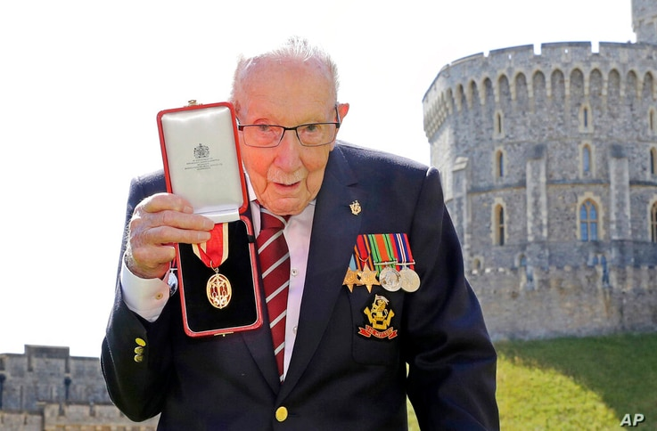 FILE - In this Friday, July 17, 2020 file photo, Captain Sir Thomas Moore poses for the media after receiving his knighthood…