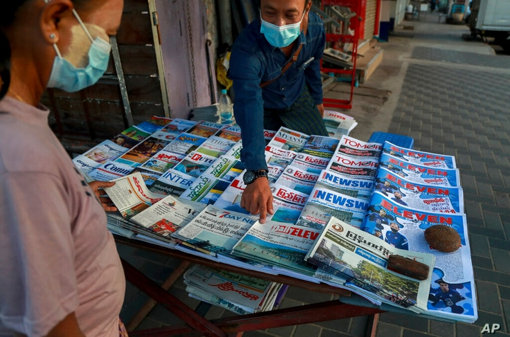 A newspaper seller points at a front-page of a newspaper in Yangon, Myanmar, Tuesday, Feb. 2, 2021. Hundreds of members of…