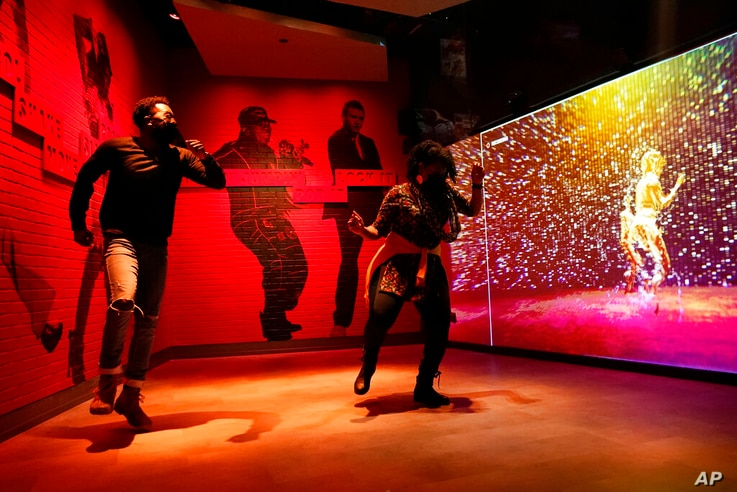 Armond Carter, left, of Atlanta, and his mother, Latonya Carter, dance together in an exhibit at the National Museum of African…