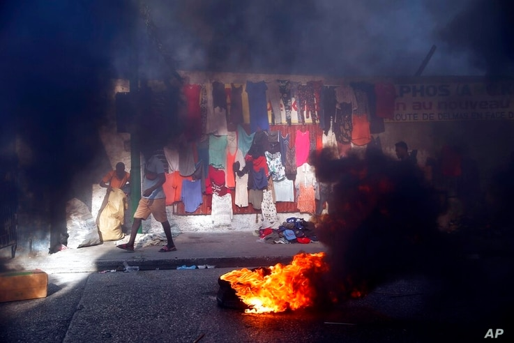 Smoke from tires set fire by protesters fills a street in Delmas where vendors sell clothing during a countrywide strike…