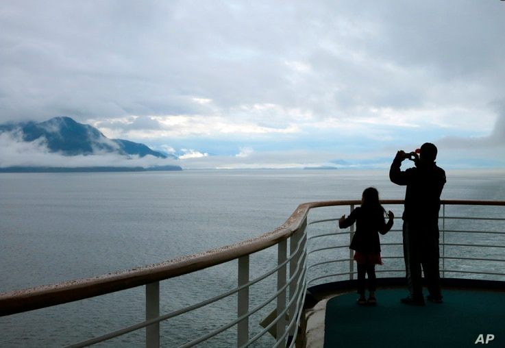 FILE - In this July 28, 2014, file photo, a cruise ship passenger takes photos of Alaska's Inside Passage. The Canadian…