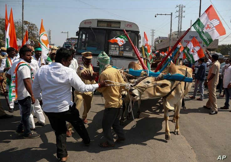 Congress party activists block a highway during a nationwide shutdown called by thousands of Indian farmers protesting new agriculture laws in Hyderabad, India, Feb. 6, 2021.