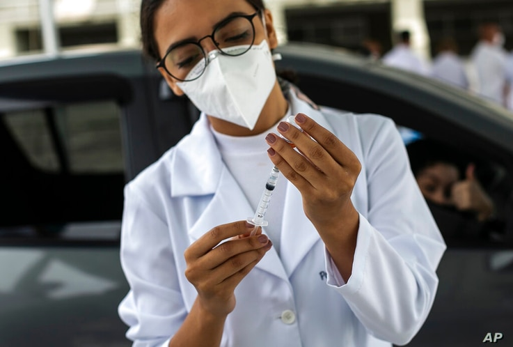 A healthcare worker prepares a dose of the China's Sinovac Biotech COVID-19 vaccine at a drive-thru vaccination site in the...
