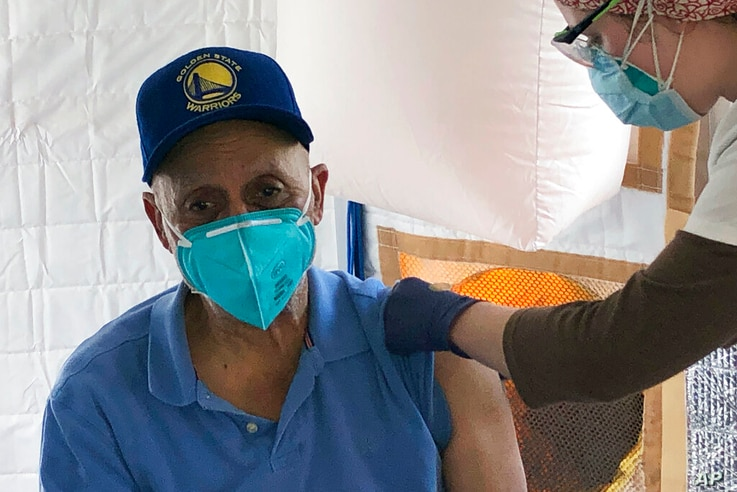 Martin Auzenne, 73, left, receives a COVID-19 vaccine shot from a health care worker at a vaccination site in the Bayview…