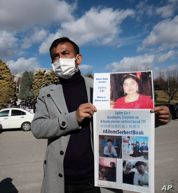 Uighur protester Mirza Ahmet Ilyasoglu holds photographs of relatives he says they have not heard from in years, speaks near…