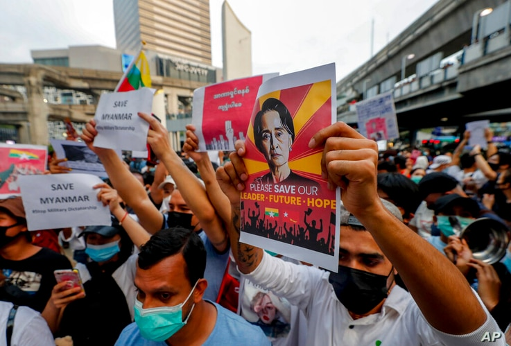 Myanmar nationals living in Thailand display pictures of detained Myanmar leader Aung San Suu Kyi during a protest against the…