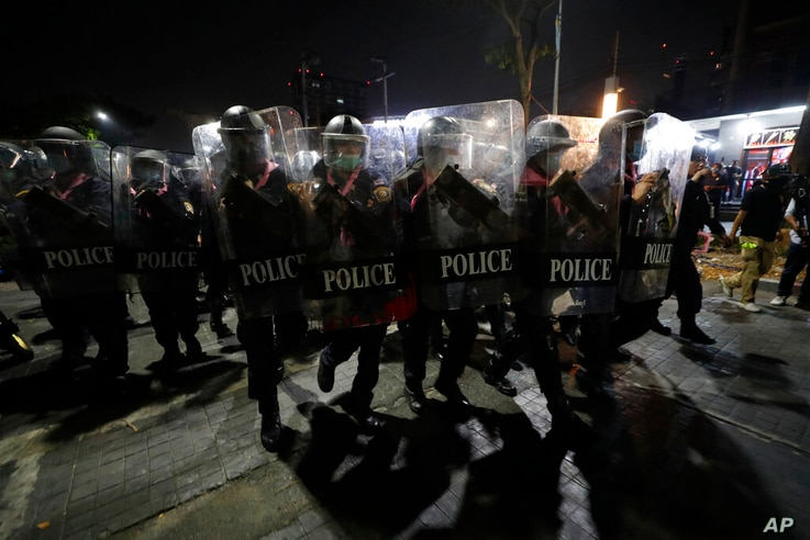 Police hold shields in formation as pro-democracy protesters demanding the release of pro-democracy activists march in Bangkok,…