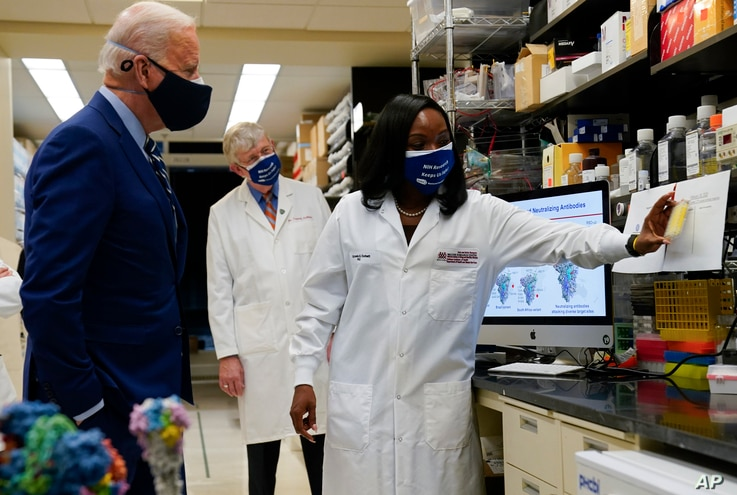 President Joe Biden listens as Kizzmekia Corbett, an immunologist with the Vaccine Research Center at the National Institutes…