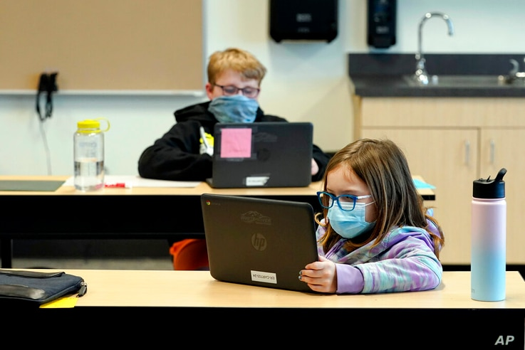 FILE - In this Feb. 2, 2021, file photo, students wear masks as they work in a fourth-grade classroom, at Elk Ridge Elementary…