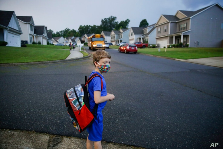 FILE - In this Aug. 3, 2020, file photo, Paul Adamus, 7, waits at the bus stop for the first day of school in Dallas, Ga. Amid…