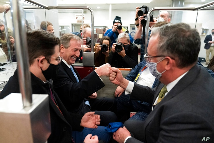 Michael van der Veen, second from left an attorney for former President Donald Trump, fist bumps a colleague as the depart on…