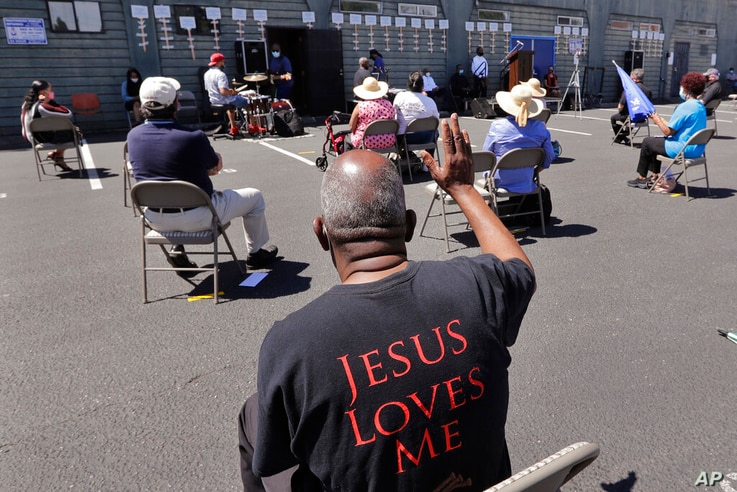 FILE - In this Sunday, July 19, 2020 file photo, church parishioners sit apart socially distanced at a prayer vigil for racial…