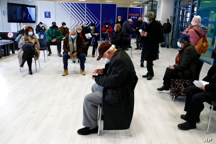 People wait at the reception hall of vaccination mega center in Athens, Monday, Feb. 15, 2021. The Promitheas center, which has…