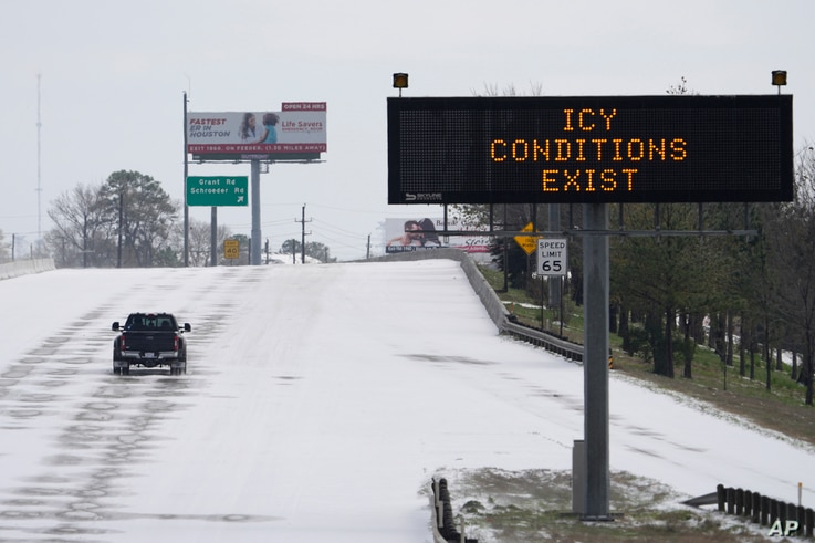 A truck drives past a highway sign Monday, Feb. 15, 2021, in Houston. A frigid blast of winter weather across the U.S. plunged…