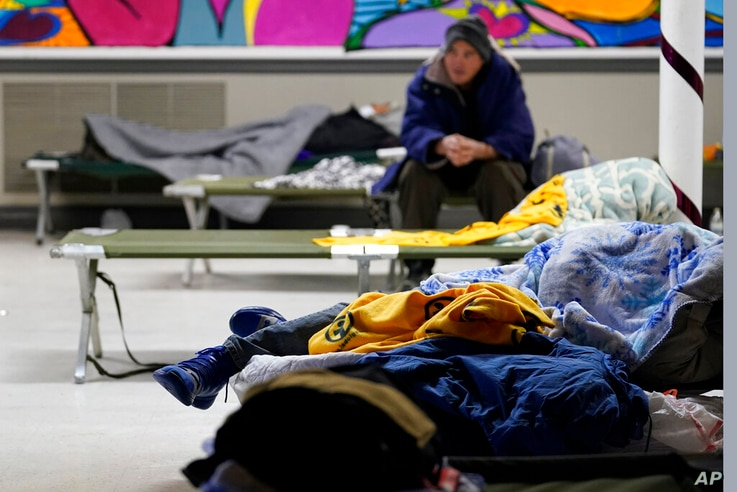 People seeking shelter from sup-freezing temperatures rest at a make-shift warming shelter at Travis Park Methodist Church,…