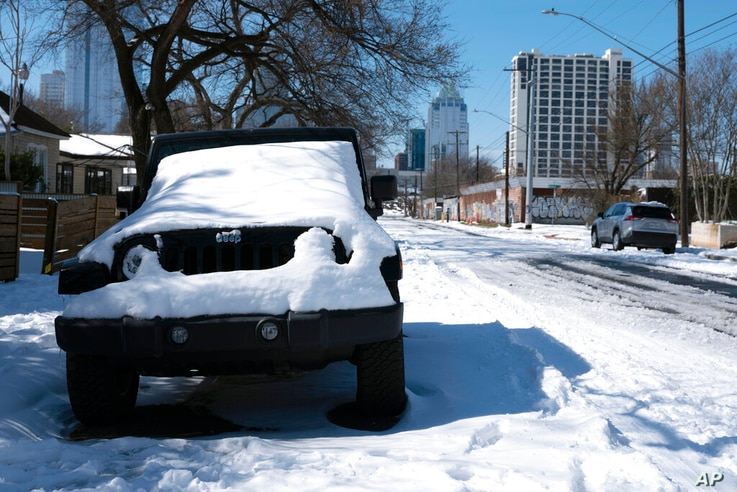 A parked Jeep is covered in snow Tuesday, Feb. 16, 2021, in Austin, Texas. Temperatures dropped into the single digits as snow…