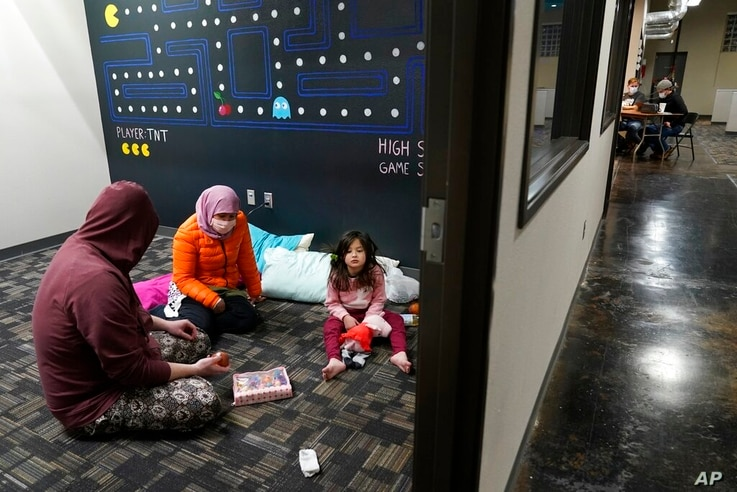 Christopher Harris, left, his wife Novi, center, and their daughter Keeva, occupy an office suite at a pop-up warming center in…