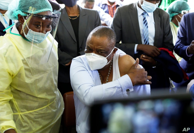 A nurse prepares to give a shot of China's Sinopharm vaccine to Zimbabwean Deputy President Constatino Chiwenga, right, at…